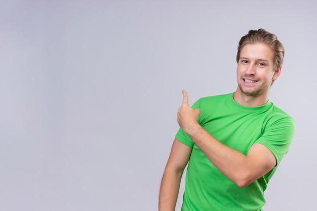 Jonge knappe man met groene t-shirt glimlachend vrolijk wijzend met de vinger naar iets achter staande over witte muur