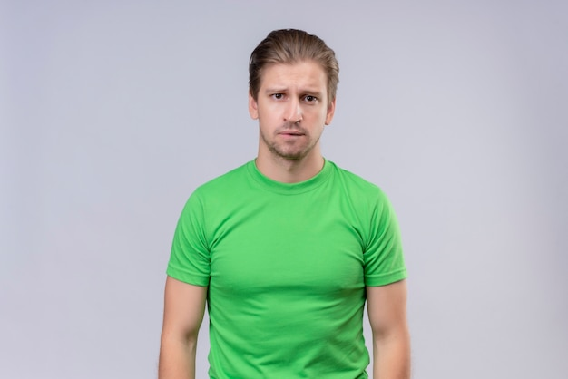 Jonge knappe man met groene t-shirt met droevige uitdrukking op gezicht staande over witte muur