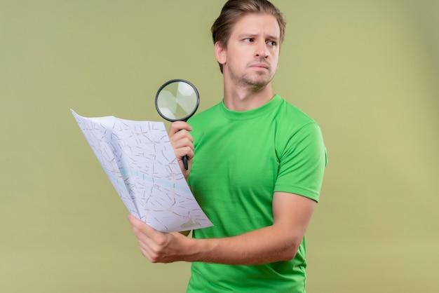 Jonge knappe man met groene t-shirt met kaart en vergrootglas met ernstige uitdrukking op gezicht opzij kijken staande over groene muur