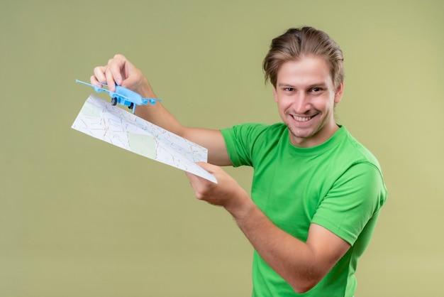 Jonge knappe man met groene t-shirt met speelgoed vliegtuig en kaart glimlachend vrolijk staande over groene muur 2