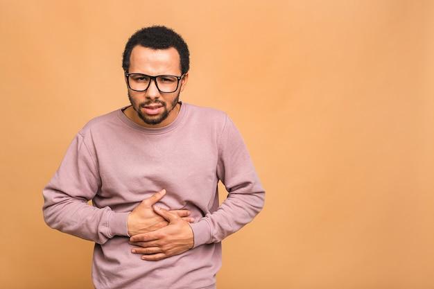 Jonge knappe man met hand op buik omdat indigestie, pijnlijke ziekte zich onwel voelen
