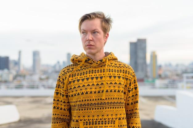 Jonge knappe man met hoodie denken tegen uitzicht over de stad