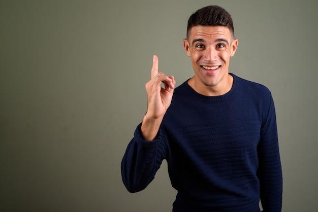 Jonge knappe man met idee wijzende vinger tegen gekleurde achtergrond