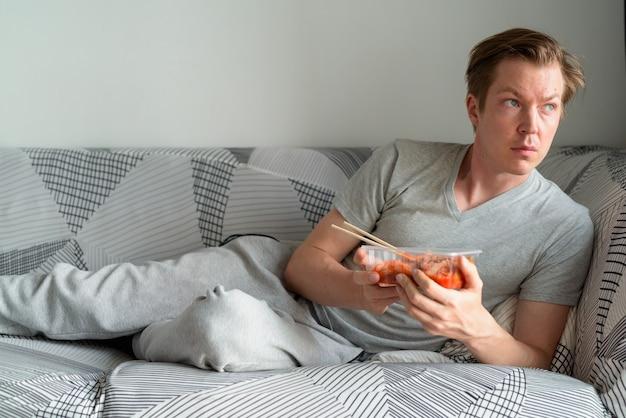 Jonge knappe man met kimchi denken en kijkt uit het raam thuis