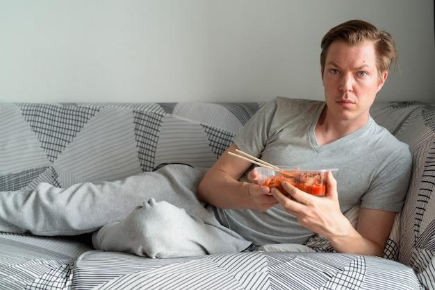 Jonge knappe man met kimchi terwijl hij thuis op de bank ligt