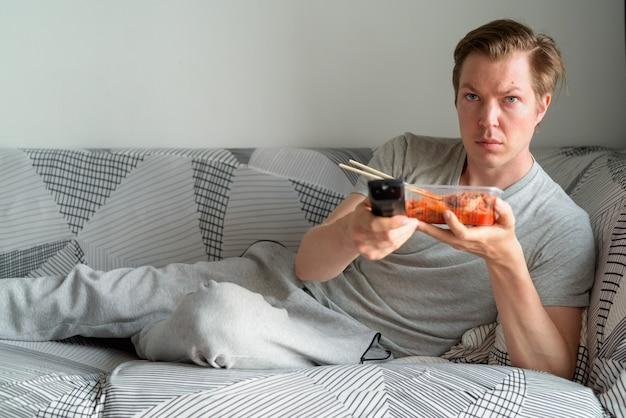 Jonge knappe man met kimchi tv kijken en thuis op de bank liggen