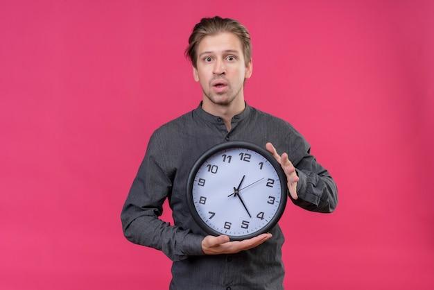 Jonge knappe man met klok verrast en verbaasd, staande over roze muur