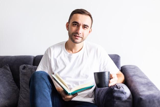Jonge knappe man met koffie tijdens het lezen van boek in de woonkamer