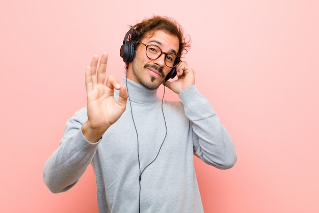 Jonge knappe man met koptelefoon tegen roze platte muur