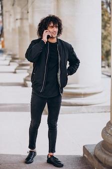 Jonge knappe man met krullend haar praten aan de telefoon