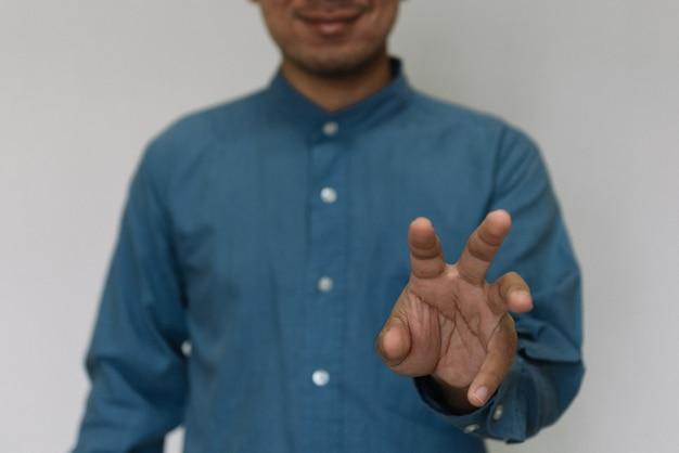 Jonge knappe man met lichtblauw shirt met ander gedrag op het werk