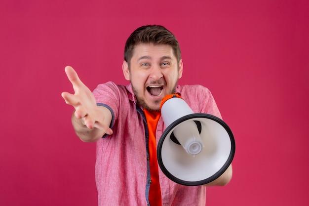 Jonge knappe man met megafoon schreeuwen naar het staande met opgeheven hand