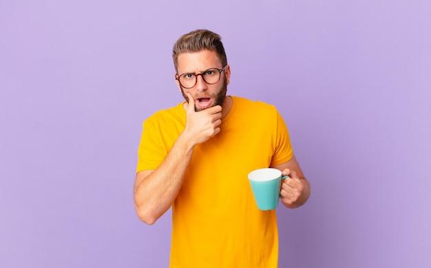 Jonge knappe man met mond en ogen wijd open en hand op de kin. en een koffiemok vasthouden