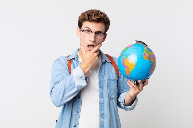 Jonge knappe man met mond en ogen wijd open en hand op de kin. student met een wereldbolkaart