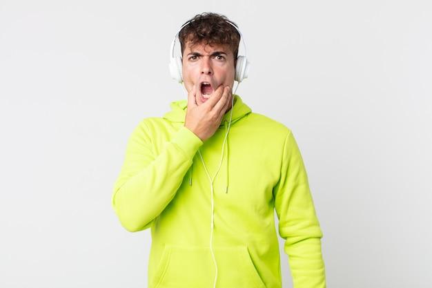 Jonge knappe man met mond en ogen wijd open en hand op kin en koptelefoon