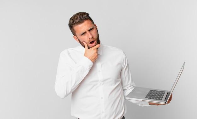 Jonge knappe man met mond en ogen wijd open en hand op kin en met een laptop