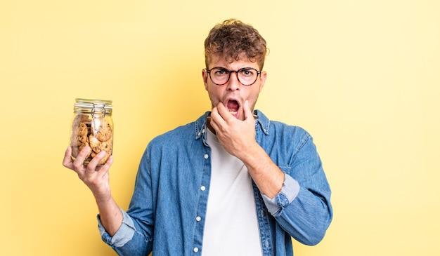 Jonge knappe man met mond en ogen wijd open en hand op kin. koekjes fles concept