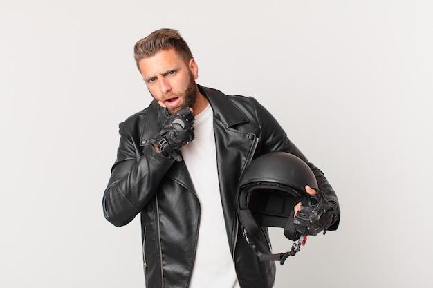Jonge knappe man met mond en ogen wijd open en hand op kin. motorhelm concept