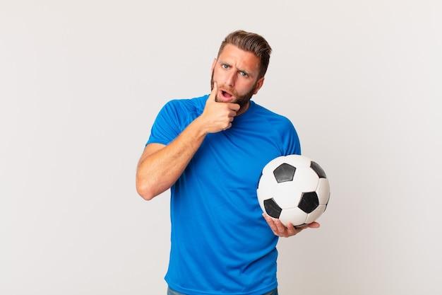 Jonge knappe man met mond en ogen wijd open en hand op kin. voetbal concept