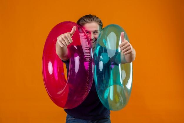 Jonge knappe man met opblaasbare ringen camera kijken met blij gezicht glimlachend vrolijk weergegeven: duimen omhoog staan over oranje achtergrond