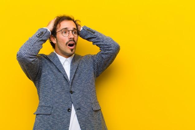 Jonge knappe man met open mond, die geschokt en geschokt kijkt vanwege een vreselijke fout, die zijn handen opheft om tegen de oranje muur te gaan