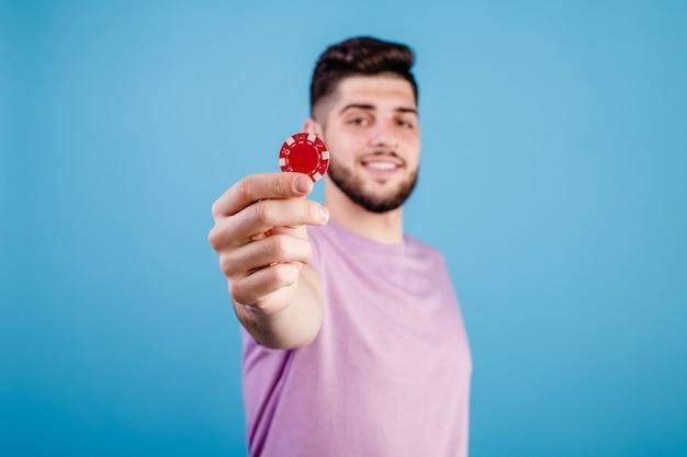 Jonge knappe man met rode pokerfiche op blauw