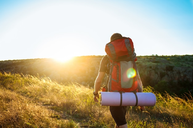 Jonge knappe man met rugzak reizen in canyon bij zonsondergang