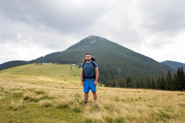 Jonge knappe man met rugzak staande in berg