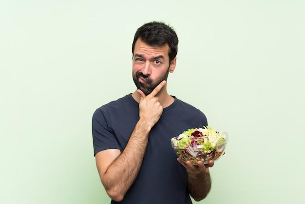 Jonge knappe man met salade over geïsoleerde groene muur denken