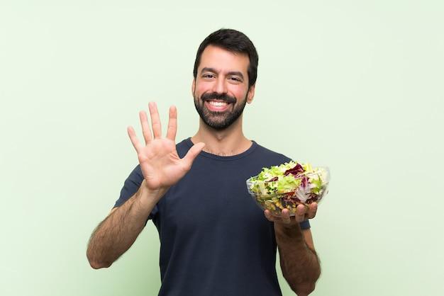 Jonge knappe man met salade over geïsoleerde groene muur die vijf met vingers telt