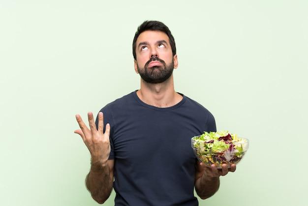 Jonge knappe man met salade over geïsoleerde groene muur gefrustreerd door een slechte situatie