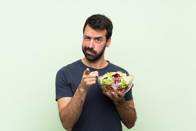 Jonge knappe man met salade over geïsoleerde groene muur gefrustreerd en wijzend op de voorkant
