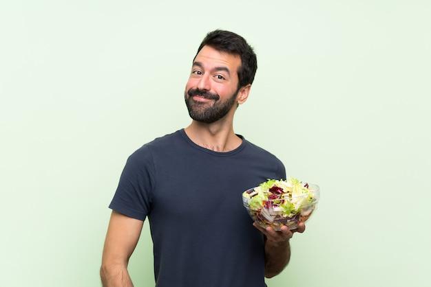 Jonge knappe man met salade over geïsoleerde groene muur lachen