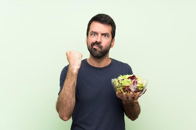 Jonge knappe man met salade over geïsoleerde groene muur met boos gebaar