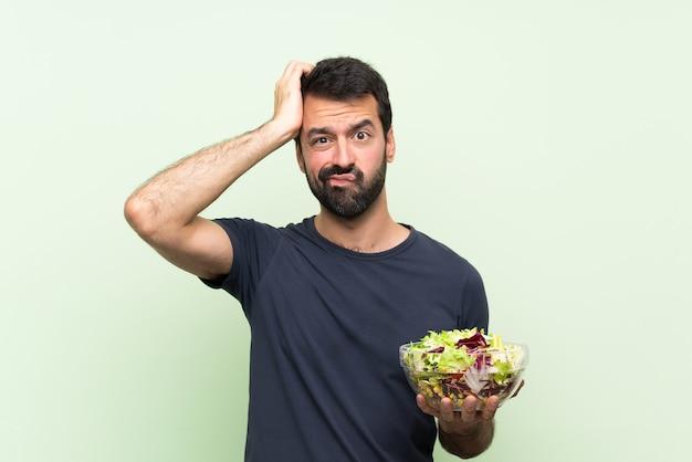 Jonge knappe man met salade over geïsoleerde groene muur met een uitdrukking van frustratie en niet begripvol