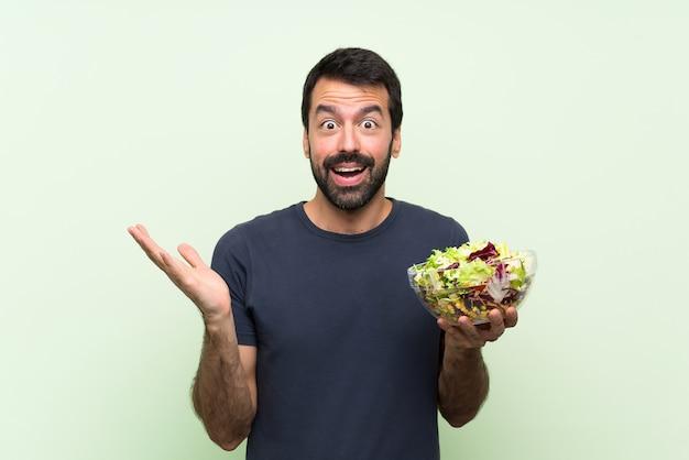 Jonge knappe man met salade over geïsoleerde groene muur met geschokte gelaatsuitdrukking