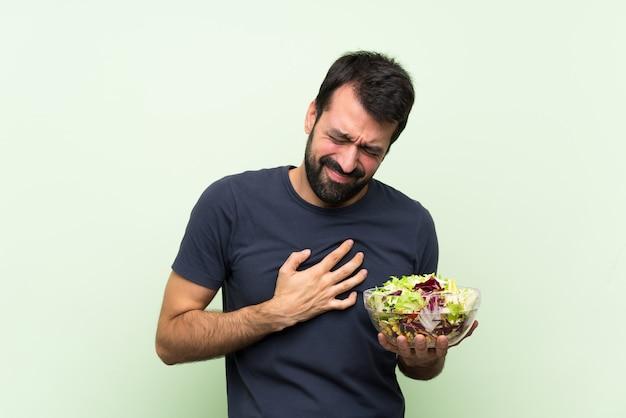 Jonge knappe man met salade over geïsoleerde groene muur met pijn in het hart