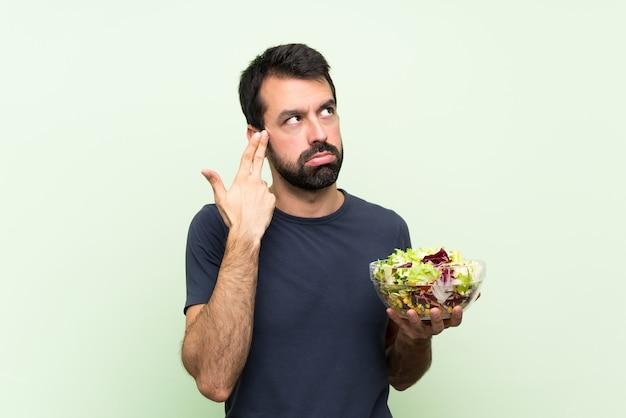 Jonge knappe man met salade over geïsoleerde groene muur met problemen die zelfmoordgebaar maken