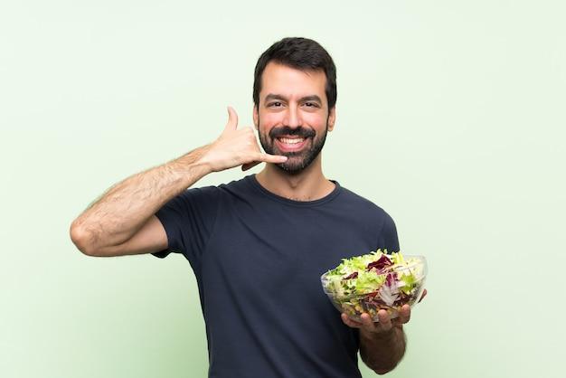 Jonge knappe man met salade over geïsoleerde groene muur telefoon gebaar maken. bel me terug teken