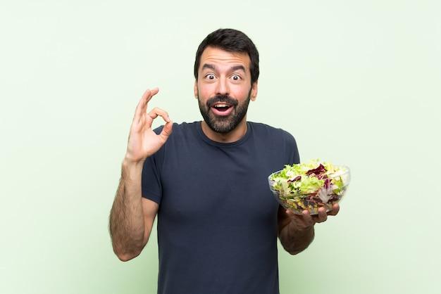 Jonge knappe man met salade over geïsoleerde groene muur verrast en het tonen van ok teken