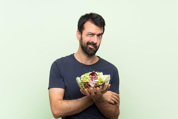 Jonge knappe man met salade over groene muur boos voelen