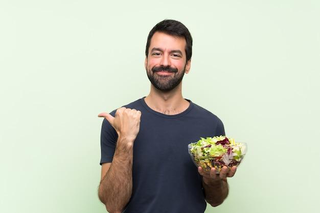 Jonge knappe man met salade wijst naar de zijkant om een product te presenteren