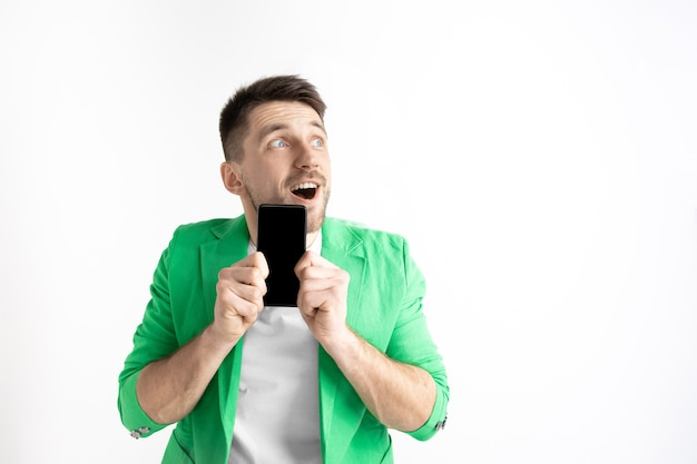 Jonge knappe man met smartphone-scherm aisolated op grijze achtergrond. menselijke emoties, gezichtsuitdrukking, reclameconcept.