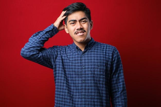 Jonge knappe man met snor die een casual shirt draagt dat over een rode achtergrond staat, verwart en verwondert zich over de vraag. onzeker met twijfel, denken met de hand op het hoofd. peinzend concept.