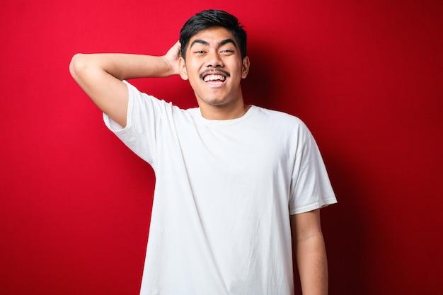 Jonge knappe man met snor die een wit t-shirt draagt dat over een rode achtergrond staat, verwart en verwondert zich over de vraag. onzeker met twijfel, denken met de hand op het hoofd. peinzend concept.