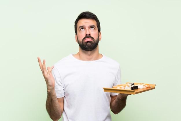 Jonge knappe man met sushi over geïsoleerde groene muur gefrustreerd door een slechte situatie