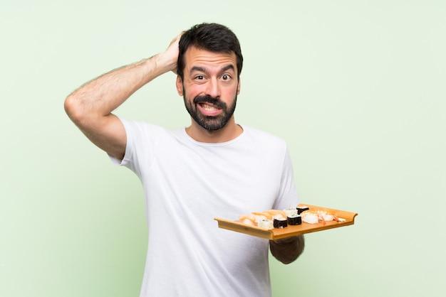 Jonge knappe man met sushi over geïsoleerde groene muur gefrustreerd en neemt handen op het hoofd