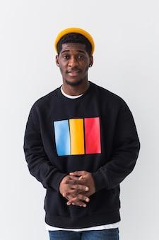 Jonge knappe man met sweatshirt tegen witte muur