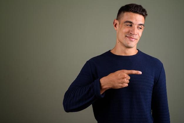 Jonge knappe man met trui tegen gekleurde achtergrond