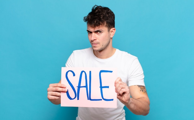 Jonge knappe man met verkoop bord